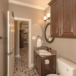 Imagen de cuarto de baño con ducha, rústico, de tamaño medio, con armarios estilo shaker, puertas de armario de madera oscura, sanitario de dos piezas, baldosas y/o azulejos marrones, baldosas y/o azulejos de travertino, paredes beige, suelo de ladrillo, lavabo bajoencimera, encimera de granito y suelo marrón