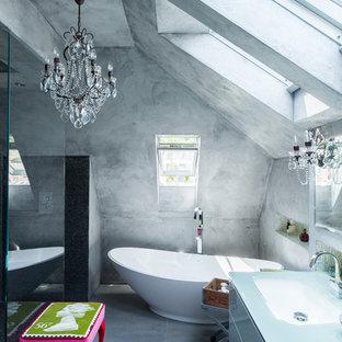 Inspiration för ett funkis en-suite badrum, med ett undermonterad handfat, släta luckor, ett fristående badkar, en kantlös dusch, grå väggar, betonggolv och bänkskiva i glas