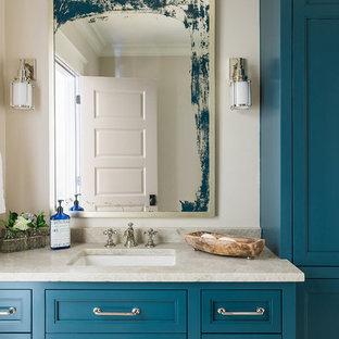 Ejemplo de cuarto de baño costero con armarios con paneles empotrados, puertas de armario azules, paredes beige, lavabo bajoencimera, encimera de granito y encimeras beige