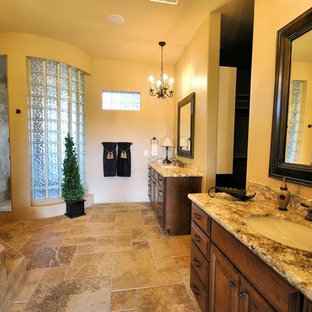 Example of a mid-sized classic master beige tile porcelain tile bathroom design in Phoenix with raised-panel cabinets, dark wood cabinets, beige walls, an undermount sink and granite countertops