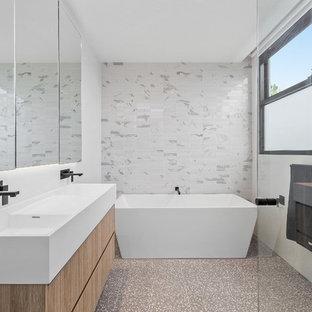 Modelo de cuarto de baño infantil, contemporáneo, de tamaño medio, con armarios con paneles lisos, puertas de armario de madera clara, bañera exenta, ducha esquinera, baldosas y/o azulejos blancos, baldosas y/o azulejos en mosaico, paredes blancas, suelo de terrazo, lavabo integrado, encimera de mármol, suelo gris, ducha con puerta con bisagras y encimeras blancas