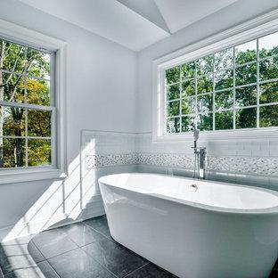 Foto di una stanza da bagno padronale tradizionale di medie dimensioni con ante in stile shaker, ante bianche, vasca freestanding, doccia ad angolo, piastrelle bianche, piastrelle di vetro, pavimento in gres porcellanato, top in quarzite, pavimento nero, porta doccia a battente e top bianco