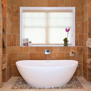 На фото: большая главная ванная комната в стиле неоклассика (современная классика) с отдельно стоящей ванной, плоскими фасадами, фасадами цвета дерева среднего тона, душем в нише, унитазом-моноблоком, бежевой плиткой, плиткой из травертина, бежевыми стенами, полом из керамогранита, настольной раковиной, стеклянной столешницей, бежевым полом, душем с распашными дверями и окном