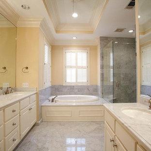 Inspiration för stora klassiska en-suite badrum, med luckor med upphöjd panel, vita skåp, en jacuzzi, en hörndusch, en toalettstol med hel cisternkåpa, stenkakel, gula väggar, marmorgolv, ett undermonterad handfat, marmorbänkskiva och vit kakel