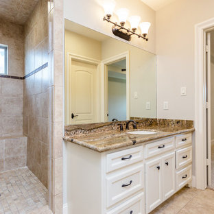 Large mediterranean bathroom in Houston with recessed-panel cabinets, white cabinets, a two-piece toilet, beige tiles, travertine tiles, beige walls, travertine flooring, a submerged sink, granite worktops, beige floors, brown worktops, a built-in shower and an open shower.