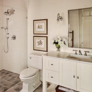 Country Duschbad mit Schrankfronten im Shaker-Stil, weißen Schränken, Duschnische, Wandtoilette mit Spülkasten, weißer Wandfarbe, Unterbauwaschbecken, grauem Boden und weißer Waschtischplatte in Milwaukee
