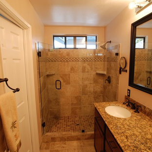 Alcove shower - mid-sized mediterranean master beige tile and stone tile porcelain floor alcove shower idea in Orange County with an undermount sink, recessed-panel cabinets, dark wood cabinets, granite countertops, a two-piece toilet and white walls