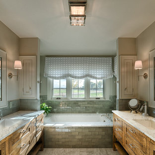 Mid-sized mountain style master green tile and glass tile drop-in bathtub photo in Denver with a drop-in sink, shaker cabinets, granite countertops, a two-piece toilet, beige walls and medium tone wood cabinets
