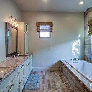 Diseño de cuarto de baño principal, de estilo americano, de tamaño medio, con armarios estilo shaker, puertas de armario blancas, baldosas y/o azulejos grises, baldosas y/o azulejos de porcelana, encimera de vidrio, bañera encastrada, ducha abierta, paredes beige, suelo de baldosas de porcelana y lavabo bajoencimera