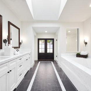 Design ideas for a large mediterranean ensuite bathroom in Orange County with recessed-panel cabinets, white cabinets, a submerged bath, white tiles, stone tiles, white walls, porcelain flooring, a submerged sink, engineered stone worktops, black floors, a hinged door and white worktops.