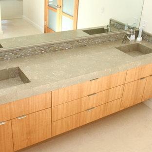 Ispirazione per una stanza da bagno padronale design di medie dimensioni con lavabo integrato, ante lisce, ante in legno scuro, top in pietra calcarea, piastrelle di vetro e pavimento in pietra calcarea