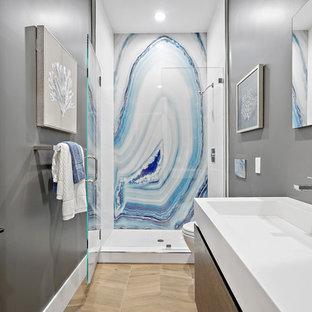 Ispirazione per una stanza da bagno con doccia minimalista di medie dimensioni con ante lisce, ante in legno scuro, doccia alcova, WC sospeso, pareti grigie, parquet chiaro, lavabo integrato, top in quarzo composito, pavimento beige, porta doccia a battente, top bianco, piastrelle blu, piastrelle bianche, lastra di pietra, un lavabo e mobile bagno sospeso