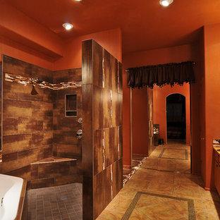 Foto di un'ampia stanza da bagno padronale design con lavabo a bacinella, ante con bugna sagomata, ante in legno scuro, top in granito, vasca sottopiano, doccia aperta, piastrelle marroni, piastrelle in gres porcellanato, pareti arancioni e pavimento in travertino