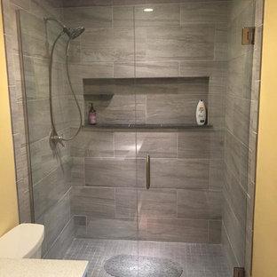 Modern inredning av ett mellanstort en-suite badrum, med grå skåp, en dusch i en alkov, en toalettstol med separat cisternkåpa, cementkakel, gula väggar, mellanmörkt trägolv, ett undermonterad handfat och bänkskiva i akrylsten