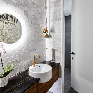 Idee per una stanza da bagno padronale contemporanea con ante lisce, ante in legno bruno, piastrelle grigie, piastrelle di marmo, pareti grigie, lavabo da incasso, pavimento nero e top nero