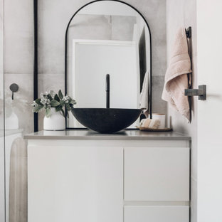Beach style bathroom in Gold Coast - Tweed with white cabinets, grey walls and a single vanity.