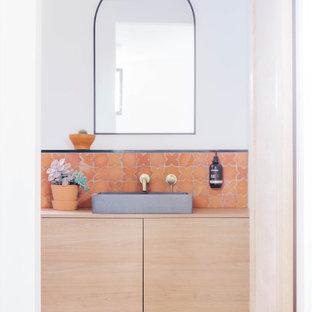 Bild på ett maritimt beige beige badrum, med släta luckor, skåp i ljust trä, orange kakel, vita väggar, ett fristående handfat, träbänkskiva och orange golv