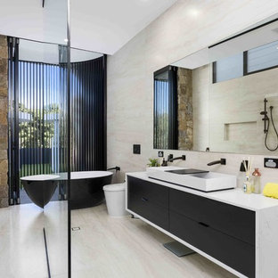 Photo of a contemporary master bathroom in Gold Coast - Tweed with flat-panel cabinets, black cabinets, a freestanding tub, an open shower, a one-piece toilet, beige tile, beige walls, a trough sink, concrete benchtops, beige floor, an open shower and grey benchtops.
