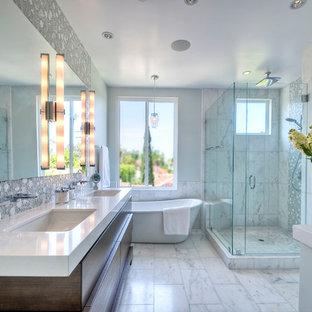 Foto de cuarto de baño principal, actual, de tamaño medio, con lavabo bajoencimera, puertas de armario de madera en tonos medios, encimera de cuarzo compacto, bañera exenta, ducha esquinera, baldosas y/o azulejos blancos, paredes grises, suelo de mármol y armarios con paneles lisos
