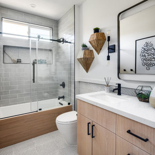 Small beach style family bathroom in Orange County with flat-panel cabinets and light wood cabinets.