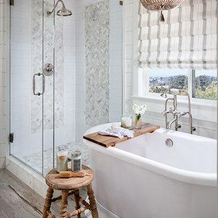 Immagine di una stanza da bagno padronale country con vasca freestanding, doccia ad angolo, piastrelle bianche, pareti bianche, pavimento in legno verniciato e porta doccia a battente