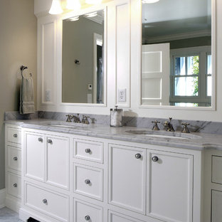 Design ideas for a large traditional master bathroom in Grand Rapids with marble benchtops, recessed-panel cabinets, white cabinets, beige walls, marble floors and an undermount sink.