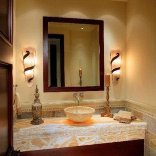 Esempio di una grande stanza da bagno mediterranea con nessun'anta, ante in legno bruno, WC a due pezzi, piastrelle multicolore, piastrelle in pietra, pareti beige, pavimento in pietra calcarea, lavabo a bacinella e top in onice