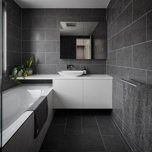 Immagine di una piccola stanza da bagno design con ante lisce, ante bianche, piastrelle nere, piastrelle in gres porcellanato, pareti nere, pavimento in gres porcellanato, lavabo a bacinella, top in quarzo composito, pavimento nero, top bianco e vasca sottopiano
