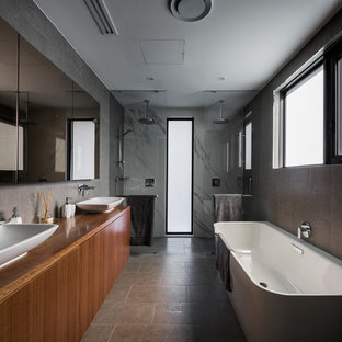 This is an example of a mid-sized contemporary bathroom in Canberra - Queanbeyan with flat-panel cabinets, medium wood cabinets, black tile, porcelain tile, black walls, porcelain floors, a vessel sink, wood benchtops, black floor, an open shower, a freestanding tub, a double shower and brown benchtops.