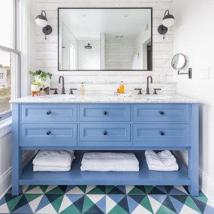 Diseño de cuarto de baño bohemio con armarios con paneles empotrados, puertas de armario azules, paredes blancas, suelo de azulejos de cemento, lavabo bajoencimera y suelo multicolor