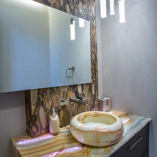 Foto de cuarto de baño principal, minimalista, grande, con armarios con paneles lisos, puertas de armario marrones, bañera exenta, paredes blancas, lavabo suspendido y encimera de ónix