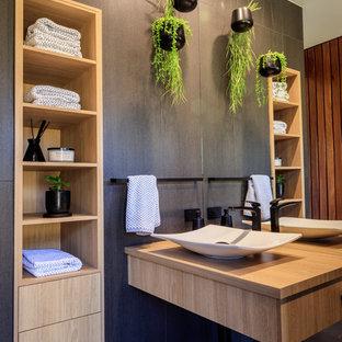Ispirazione per una stanza da bagno design con piastrelle nere, pareti grigie, lavabo a bacinella, top in legno, pavimento nero e top beige