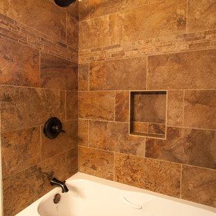 カルガリーの小さいトラディショナルスタイルのおしゃれな浴室 (オーバーカウンターシンク、家具調キャビネット、茶色いキャビネット、御影石の洗面台、アルコーブ型浴槽、シャワー付き浴槽、茶色いタイル、石タイル、茶色い壁、セラミックタイルの床) の写真