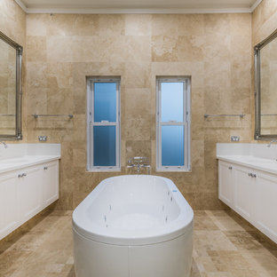 Design ideas for a victorian master bathroom in Perth with recessed-panel cabinets, white cabinets, a freestanding tub, beige tile, beige walls, an undermount sink, beige floor and white benchtops.