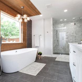 Imagen de cuarto de baño principal, contemporáneo, grande, con armarios estilo shaker, puertas de armario blancas, bañera exenta, ducha doble, baldosas y/o azulejos grises, baldosas y/o azulejos de mármol, paredes grises, suelo de pizarra, lavabo bajoencimera, encimera de cuarzo compacto, suelo gris, ducha con puerta con bisagras y encimeras blancas