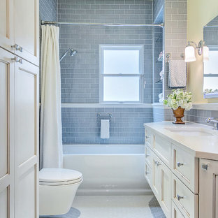 Example of a small transitional gray tile and ceramic tile ceramic floor bathroom design in Dallas with an undermount sink, recessed-panel cabinets, white cabinets, engineered quartz countertops, a wall-mount toilet and white walls