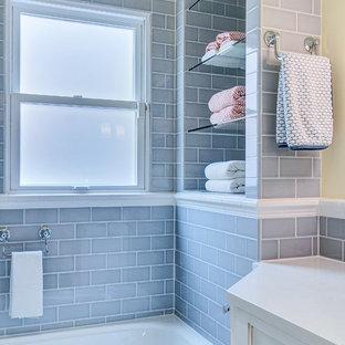 Klassisk inredning av ett litet badrum för barn, med ett undermonterad handfat, luckor med infälld panel, vita skåp, bänkskiva i kvarts, ett badkar i en alkov, en dusch/badkar-kombination, en vägghängd toalettstol, grå kakel, keramikplattor, klinkergolv i keramik och gula väggar