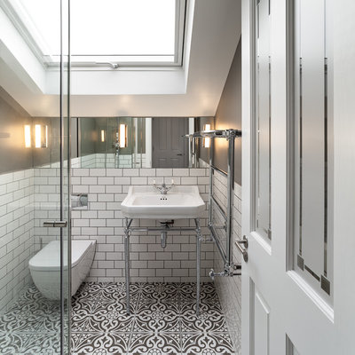 Example of a small ornate white tile and subway tile ceramic tile and multicolored floor bathroom design in London with a wall-mount toilet, gray walls and a console sink