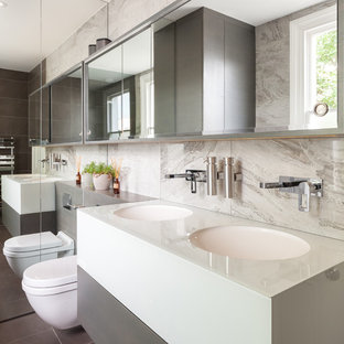 Photo of a large contemporary family bathroom in London with flat-panel cabinets, grey cabinets, a built-in bath, a walk-in shower, a wall mounted toilet, brown tiles, porcelain tiles, multi-coloured walls, ceramic flooring, a built-in sink, glass worktops, brown floors, an open shower and white worktops.