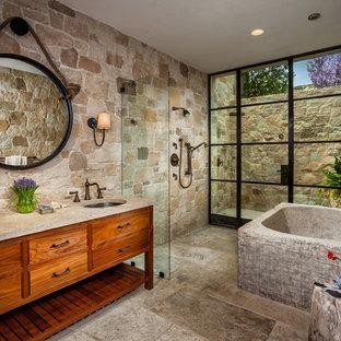 Ispirazione per una grande stanza da bagno padronale mediterranea con consolle stile comò, ante in legno scuro, doccia aperta, piastrelle beige, pareti beige, lavabo sottopiano, pavimento beige, doccia aperta, vasca freestanding e piastrelle in pietra