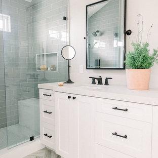 Esempio di una stanza da bagno padronale country di medie dimensioni con ante in stile shaker, ante bianche, doccia alcova, WC monopezzo, piastrelle grigie, piastrelle di vetro, pareti grigie, pavimento in gres porcellanato, lavabo sottopiano, top in quarzo composito, pavimento beige, porta doccia a battente e top bianco