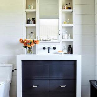 Bild på ett litet maritimt badrum för barn, med svarta skåp, ett badkar i en alkov, en dusch/badkar-kombination, vita väggar, klinkergolv i porslin och bänkskiva i kvarts