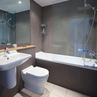 Идея дизайна: маленькая детская ванная комната в современном стиле с накладной ванной, душем над ванной, унитазом-моноблоком, коричневой плиткой, плиткой мозаикой, коричневыми стенами, полом из керамогранита, подвесной раковиной, столешницей из дерева, бежевым полом и душем с распашными дверями