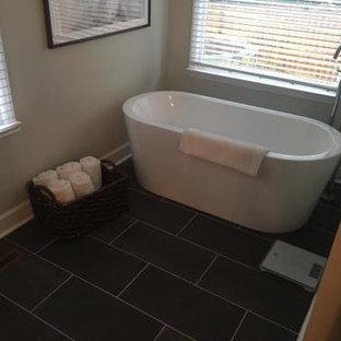 シャーロットの中サイズのモダンスタイルのおしゃれなマスターバスルーム (家具調キャビネット、白いキャビネット、置き型浴槽、コーナー設置型シャワー、分離型トイレ、グレーのタイル、セラミックタイル、ベージュの壁、セラミックタイルの床、アンダーカウンター洗面器、人工大理石カウンター、黒い床、開き戸のシャワー、ベージュのカウンター) の写真