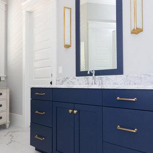 Ejemplo de cuarto de baño principal, costero, de tamaño medio, con armarios tipo mueble, puertas de armario azules, bañera exenta, ducha empotrada, sanitario de dos piezas, baldosas y/o azulejos blancos, baldosas y/o azulejos de mármol, paredes azules, suelo de mármol, lavabo sobreencimera, encimera de mármol, suelo blanco, ducha con puerta con bisagras y encimeras blancas