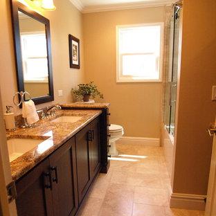 ニューアークの中サイズのトランジショナルスタイルのおしゃれなマスターバスルーム (フラットパネル扉のキャビネット、茶色いキャビネット、アルコーブ型浴槽、シャワー付き浴槽、ベージュのタイル、トラバーチンタイル、ベージュの壁、セラミックタイルの床、アンダーカウンター洗面器、御影石の洗面台、ベージュの床、引戸のシャワー、分離型トイレ) の写真