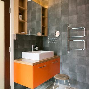 Foto de cuarto de baño con ducha, retro, con armarios con paneles lisos, puertas de armario naranjas, baldosas y/o azulejos grises, paredes grises, suelo de madera clara, lavabo sobreencimera, encimera de madera y encimeras marrones
