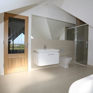 Inspiration for a medium sized contemporary bathroom in Essex with flat-panel cabinets, white cabinets, a freestanding bath, a wall mounted toilet, beige tiles, porcelain tiles, white walls, porcelain flooring, a wall-mounted sink, laminate worktops, beige floors, a hinged door and white worktops.
