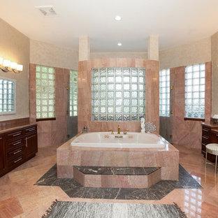 Modelo de cuarto de baño principal, clásico renovado, grande, con armarios con paneles con relieve, puertas de armario de madera oscura, bañera encastrada, baldosas y/o azulejos beige, baldosas y/o azulejos rosa, baldosas y/o azulejos de travertino, paredes beige, suelo de travertino, lavabo bajoencimera y encimera de granito