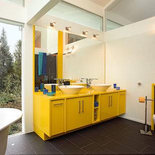 Esempio di una grande stanza da bagno design con pareti gialle, ante gialle, vasca freestanding, piastrelle nere e lavabo a bacinella